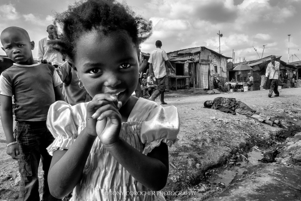 Contrasts: Curiosity & diffidence, desperation & indifference | Through the streets of Mathare Slum (Nairobi). The contrast between the innocent beauty of the young girl, the vivid diffidence of the boy behind her, the finality of the desperation shown by the man on the ground and the indifference of the people passing by. This is the ensemble of feelings that runs through these slums every day.